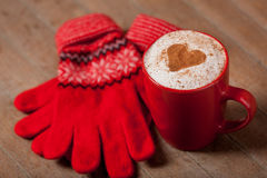 Photo of cup of coffee and warm gloves on the wonderful brown  Royalty Free Stock Images