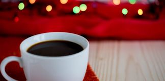 Photo of a cup with coffee on a wooden background with space for copispeys. Frame for a banner with coffee and Christmas garland. stock image