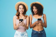 Photo of curious african american woman peeking at mobile phone. Photo of curious african american women peeking at mobile phone of caucasian ginger girl in stock image
