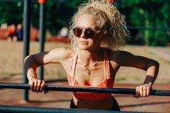 Photo curly blonde sports pulls up on sports simulator in park stock photos
