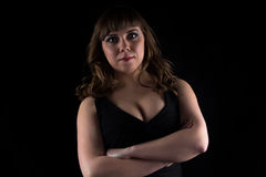 Photo of curvy woman with arms crossed. On black background Royalty Free Stock Images