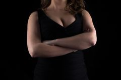 Photo curvy woman's bust with arms crossed. Photo of curvy woman's bust with arms crossed on black background royalty free stock image