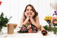 Cheerful florist woman with flowers in workshop. Photo of cute cheerful florist woman standing near table working with flowers in workshop. Looking camera Stock Images