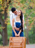 Photo of cute couple holding suitcase and kissing on the wonderf Royalty Free Stock Photo