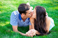 Photo of cute couple kissing and lying on the grass in the field Royalty Free Stock Photos