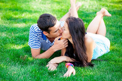 Photo of cute couple kissing and lying on the grass in the field Stock Photo