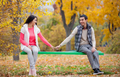 Photo of cute couple sitting on the bench and holding hands on t Stock Photography