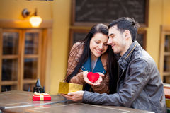 Photo of cute couple sitting on the bench and holding heart shap Stock Photography