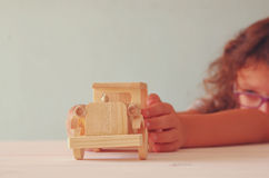 Photo of cute kid playing with old wooden toy car Stock Photo