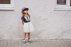 Cute little capricious girl on the street Stock Image