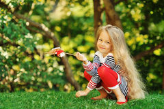 Photo of cute little girl sitting on green grass Royalty Free Stock Images