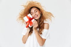 Photo of cute lovely girl 20s wearing big straw hat smiling and. Holding gift box with red ribbon isolated over white background stock photo