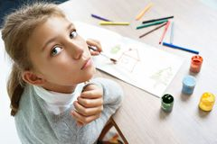 Photo of cute schoolgirl doing homework. Lonely girl is drawing. Photo of cute schoolgirl doing homework. Education concept stock images
