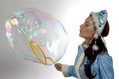 Photo of cute snow maiden blowing soap bubbles Stock Photo