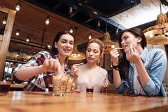 Photo d'angle faible de société féminine tout en mangeant des casse-croûte Photo libre de droits