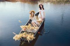 Photo d'art d'imagination de belles filles se situant dans le bateau Photographie stock libre de droits
