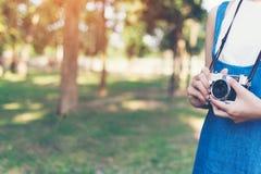 Photo d'automne de vintage avec la fille se tenant en parc avec le vieil appareil-photo Photos libres de droits