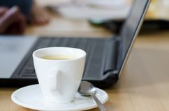Photo d'ordinateur portable avec la tasse du café et du bloc-notes sur la table en bois sur b Images stock