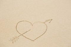 Photo d'un coeur percé avec une flèche sur le sable humide de plage Photos stock