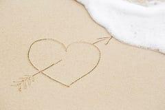 Photo d'un coeur percé avec une flèche sur le sable humide de plage Photos libres de droits