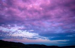 Photo d'un coucher du soleil violet avec des nuages Photographie stock libre de droits