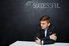Photo d'un homme triste au-dessus de conseil noir avec le texte non réussi Photos stock