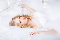 Photo d'une belle jeune mariée blonde dans une robe de mariage luxueuse dans l'intérieur photo stock
