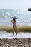 Photo d'une jeune fille dans un chapeau et un maillot de bain par la mer photos libres de droits