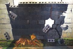 Photo of 3D Wall Painting of Street Dog breast feeding her little puppies under the shade of the falling concrete wall. royalty free stock photos