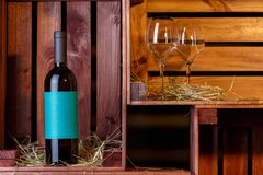 Photo of dark bottle with blue label, two wine glasses in wooden boxes stock images