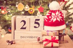Photo, date 25 décembre, cadeaux avec le traîneau et chapeau de vintage, arbre de Noël avec la décoration, concept de fête de tem Image libre de droits