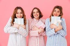 Photo de amies de sourire 20s dans l'usage à la maison tenant le boîte-cadeau Photos stock
