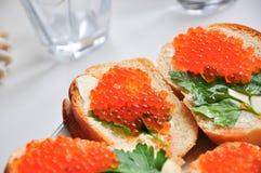 Photo de baguette avec le caviar rouge sur la table blanche Images libres de droits