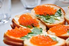 Photo de baguette avec le caviar rouge sur la table blanche Photographie stock