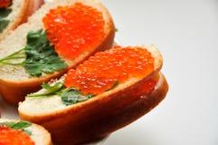 Photo de baguette avec le caviar rouge sur la table blanche Photographie stock libre de droits