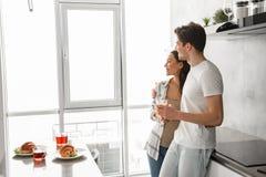 Photo de beaux couples souriant, et regardant par la grande fenêtre Photos stock