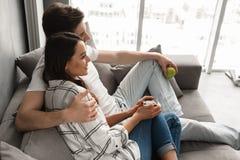 Photo de bel homme et de femme de couples s'asseyant sur le sofa dans les apartmen Photographie stock libre de droits