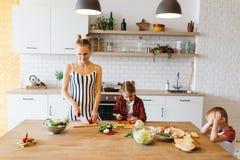 Photo de belle femme avec ses légumes de coupe de fille dans la cuisine Image libre de droits