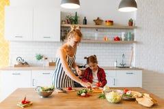 Photo de belle femme avec ses légumes de coupe de fille dans la cuisine Photographie stock