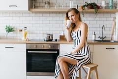 Photo de belle femme dans la robe longtemps barrée dans la cuisine Images stock