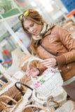 Photo de belle jeune femme tenant un panier blanc dans des ses mains semblant le sourire heureux dans le supermarché ou le magasi Photographie stock libre de droits