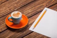 Photo de belle tasse bleue de café et de feuille de papier avec du pe Image stock