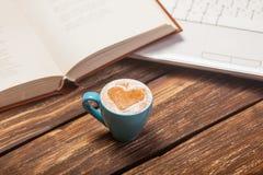 Photo de belle tasse de café, de carnet et d'ordinateur portable sur gagné Photographie stock libre de droits