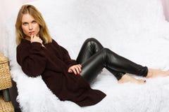 Photo de blonde dans le chandail se trouvant sur la couverture blanche de fourrure Photo stock