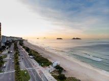 Photo de bourdon de lever de soleil en plage et promenade de Barra da Tijuca, d'Ilhas Tijucas et de Cagarras à l'arrière-plan, Ri Photographie stock