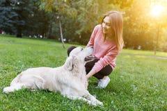 Photo de brune avec le chien se trouvant sur la pelouse Effet de lumière du soleil Images libres de droits