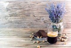 Photo de café noir parfumé dans une tasse en verre à côté des gâteaux de chocolat, des noisettes et d'un bouquet de lavande sur u image libre de droits