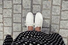 Photo de concept des jambes marchant, Selfie des pieds dans l'espadrille blanche sur le fond de trottoir de roche, vue supérieure Image libre de droits