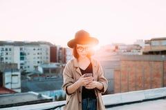 Photo de coucher du soleil de la femme à l'aide du smartphone Photo libre de droits