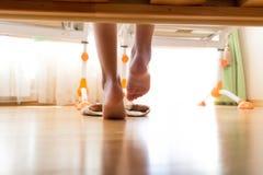 Photo de dessous le lit sur les pieds femelles mettant sur des pantoufles Images libres de droits
